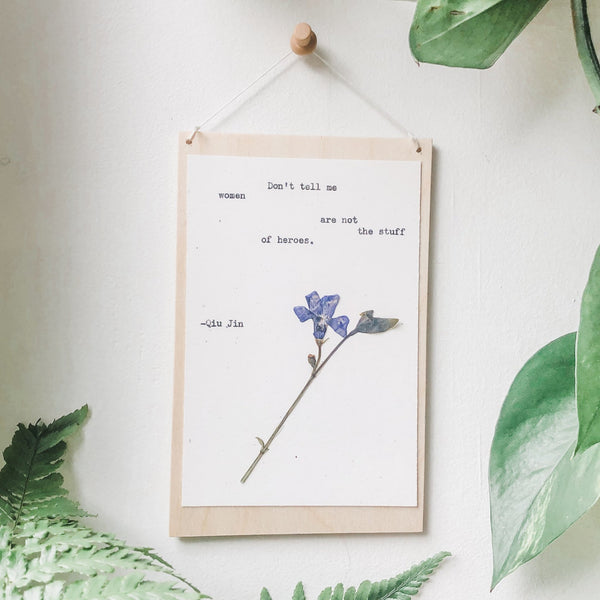 qiu jin, don't tell me women are not the stuff of heroes quote typed in typewriter font on white paper, mounted on birch wood and paired with a pressed flower. handmade décor by flora & phrase