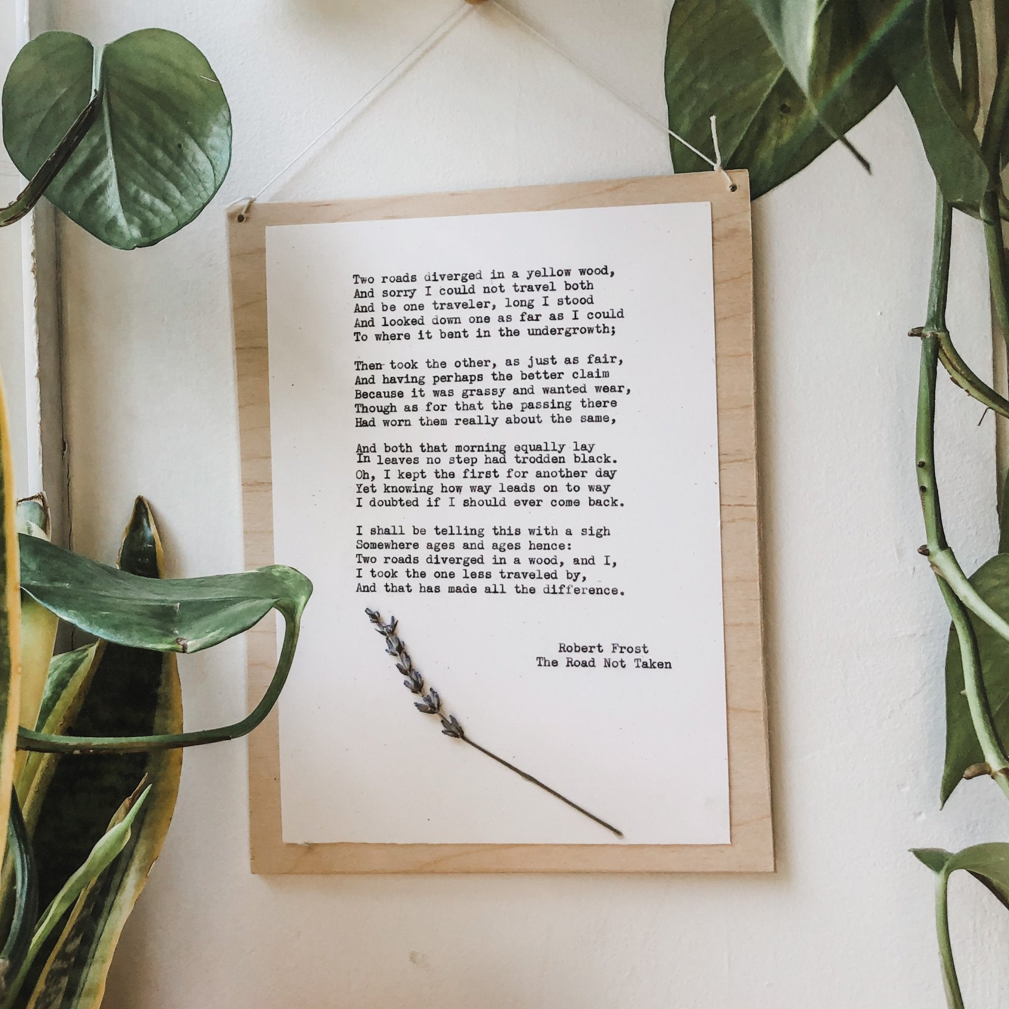 robert frost, stopping by woods on a snowy evening poem typed in typewriter font on white paper, mounted on birch wood and paired with a pressed flower. handmade décor by flora & phrase