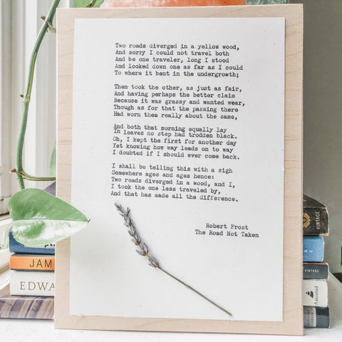 robert frost, the road not taken quote typed in typewriter font on white paper, mounted on birch wood and paired with a pressed flower. handmade décor by flora & phrase