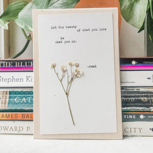 rumi, let the beauty of what you love be what you do quote typed in typewriter font on white paper, mounted on birch wood and paired with a pressed flower. handmade décor by flora & phrase