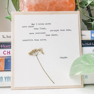 sappho, may I write words more naked than flesh quote typed in typewriter font on white paper, mounted on birch wood and paired with a pressed flower. handmade décor by flora & phrase