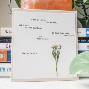 sarah grimke, I ask no favor for my sex quote typed in typewriter font on white paper, mounted on birch wood and paired with a pressed flower. handmade décor by flora & phrase