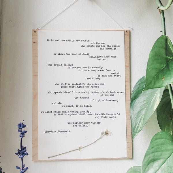 theodore roosevelt, daring greatly quote typed in typewriter font on white paper, mounted on birch wood and paired with a pressed flower. handmade décor by flora & phrase