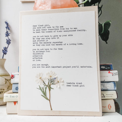 tomicia blunt, dear black girl quote typed in typewriter font on white paper, mounted on birch wood and paired with a pressed flower. handmade décor by flora & phrase