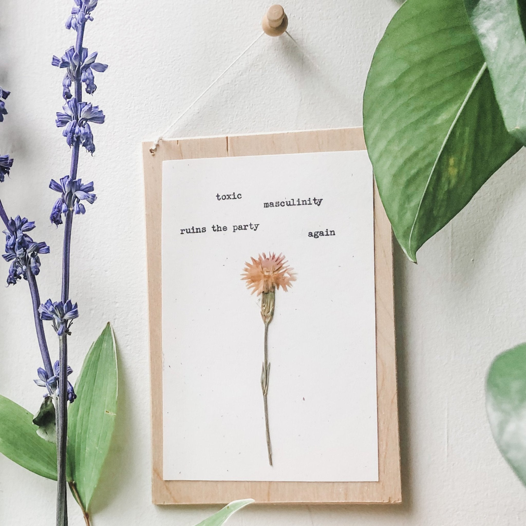 toxic masculinity ruins the party again quote typed in typewriter font on white paper, mounted on birch wood and paired with a pressed flower. handmade décor by flora & phrase