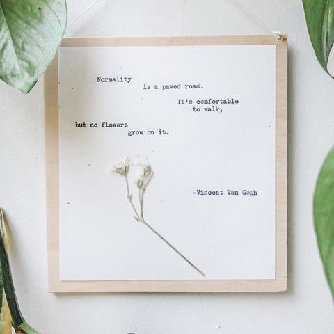 vincent van gogh, normality is a paved road quote typed in typewriter font on white paper, mounted on birch wood and paired with a pressed flower. handmade décor by flora & phrase