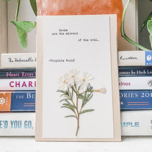 virginia woolf, books are the mirrors of the soul quote typed in typewriter font on white paper, mounted on birch wood and paired with a pressed flower. handmade décor by flora & phrase