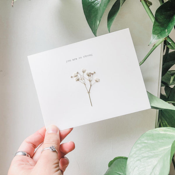 you are so strong typed in typewriter font on a white greeting card, paired with a pressed flower. handmade décor by flora & phrase