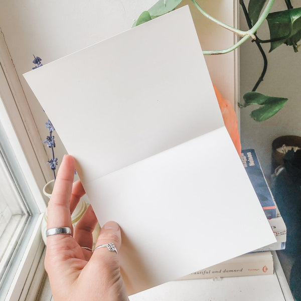 greeting card held open by a hand, blank inside.