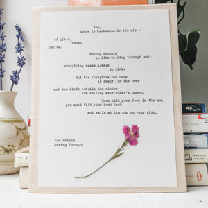 zoe branch, moving forward poem typed in typewriter font on white paper, mounted on birch wood and paired with a pressed flower. handmade décor by flora & phrase