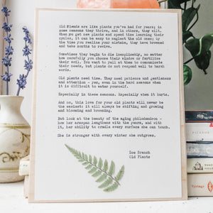 zoe branch, old plants poem typed in typewriter font on white paper, mounted on birch wood and paired with a pressed flower. handmade décor by flora & phrase