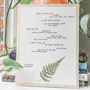 zoe branch, propagate poem typed in typewriter font on white paper, mounted on birch wood and paired with a pressed flower. handmade décor by flora & phrase
