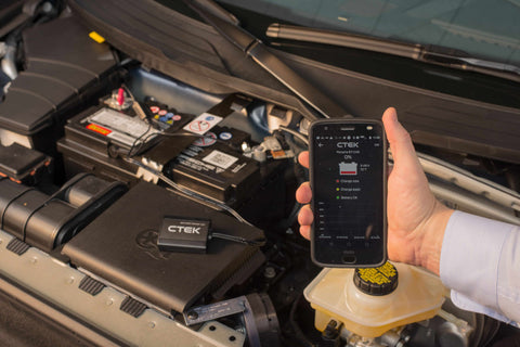 Hand holding a smartphone with the CTEK battery sense app in front of the open hood of a car to check the battery status