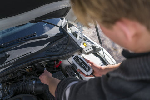 Man using a CTEK CT5 Time To Go battery charger on his car battery