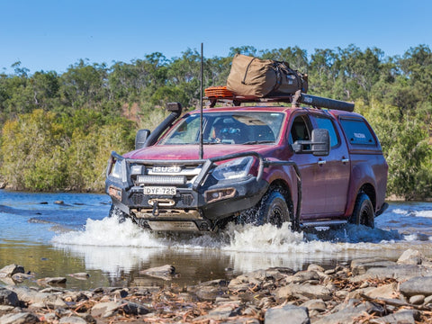Red offroad truck camper crossing a stream of water