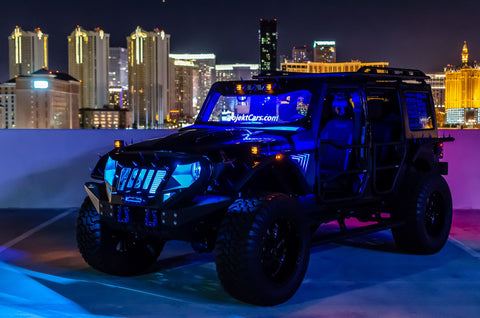 Nightime image of Jeep parked on a rooftop with blue lights