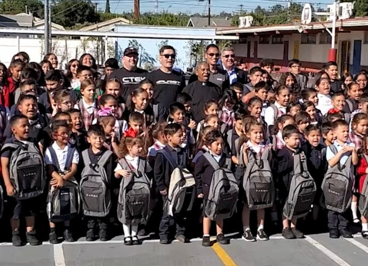 Purist Group distributes backpacks to students
