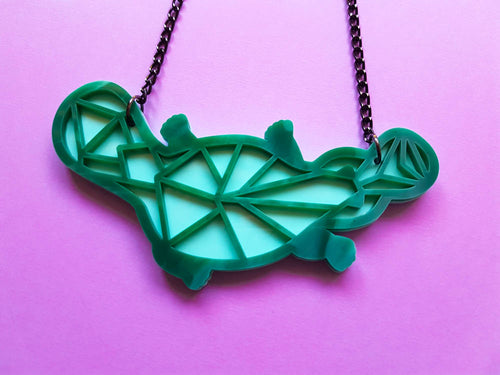 Green geometric platypus acrylic necklace.