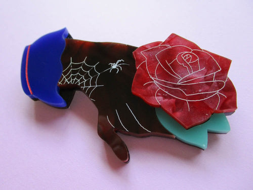 Fancy hand acrylic brooch holding a red rose.