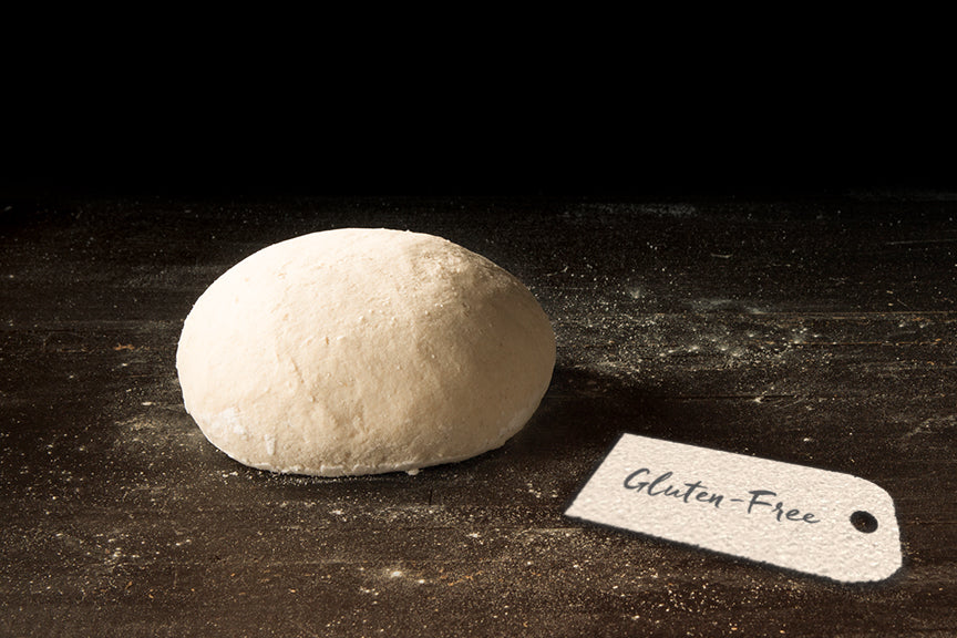 Pizza dough ball on a wood background with a rustic paper tag that says Gluten-Free