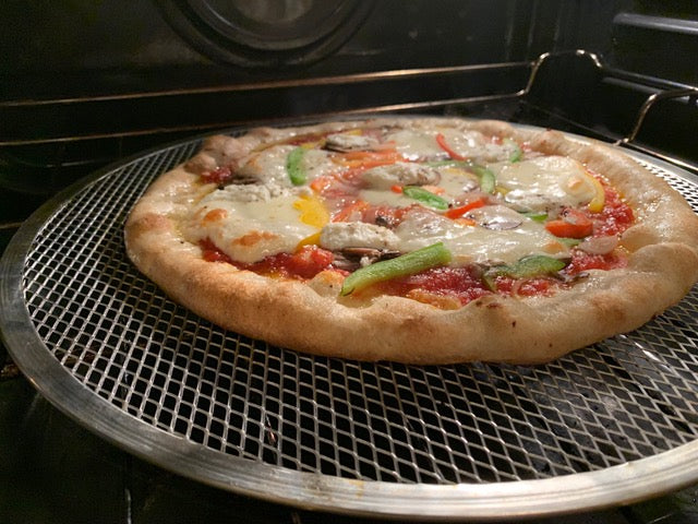 Freshly Baked Veggie Pizza with a Rising Crust on a Pizza Screen in an Oven