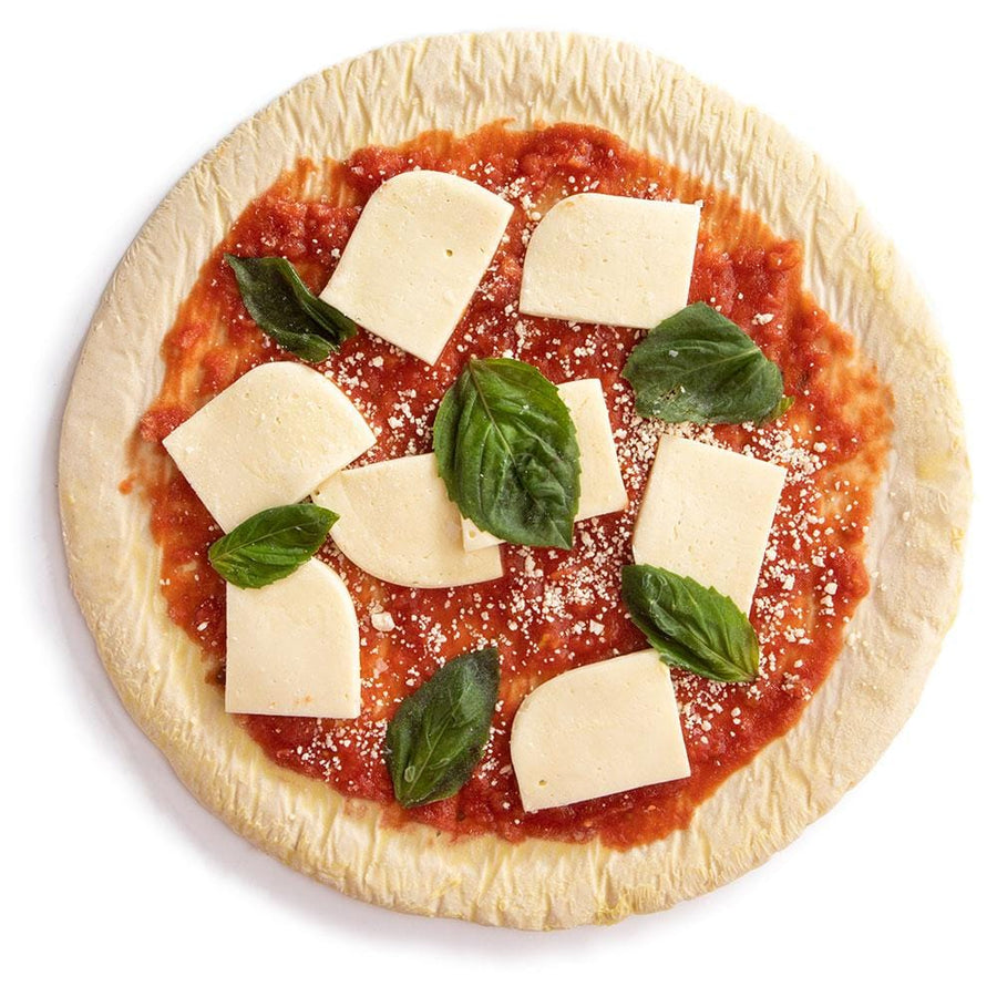 Unbaked Etalia Margherita pizza on a white background with tomatoes and fresh basil from the top down