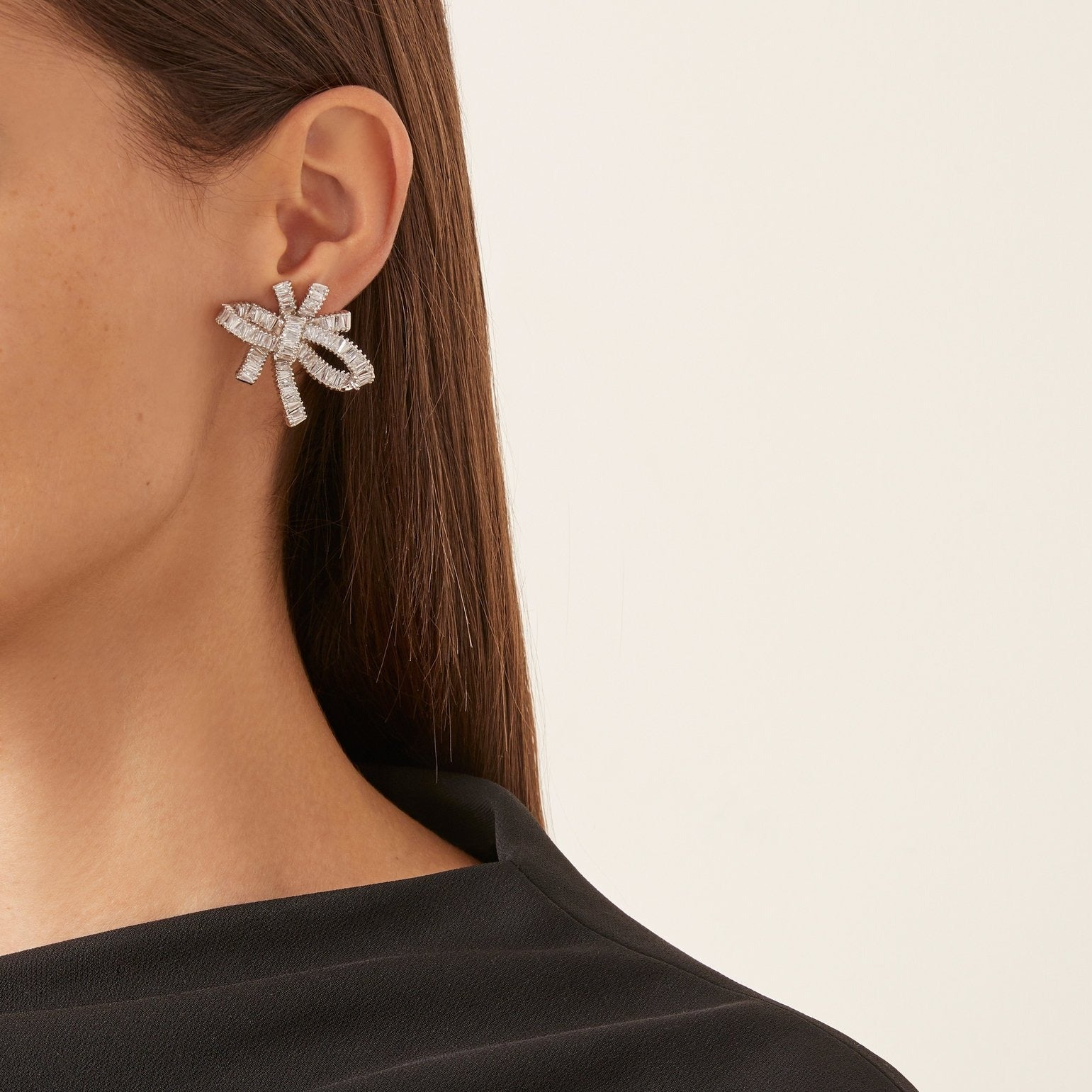 THE FALLON BAGUETTE BOW CLUSTER EARRINGS IN RHODIUM. Statement bow earrings made from plated brass and cubic zirconia.