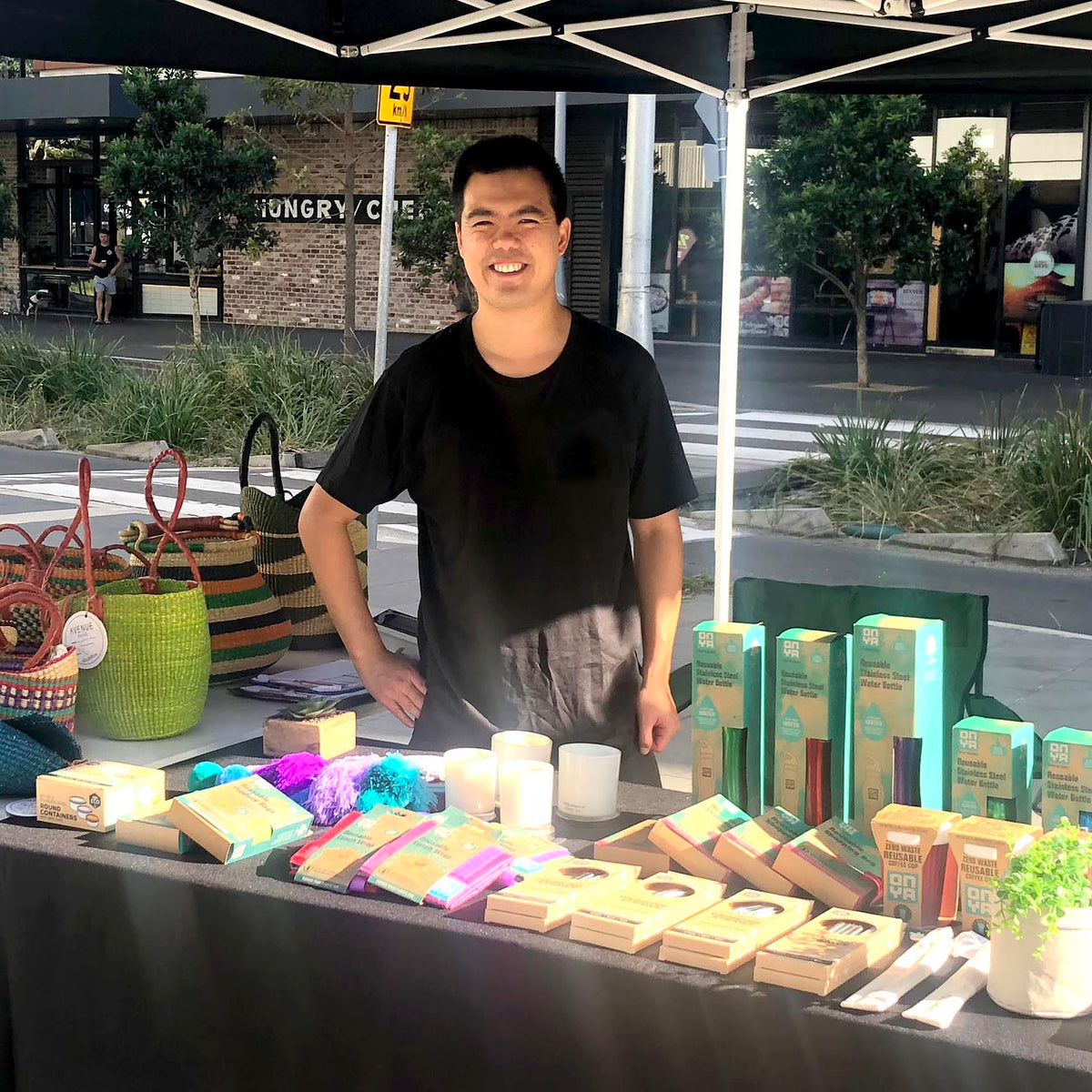 Young man with dark hair wearing a black tshirt standing behind a table filled with products smiling