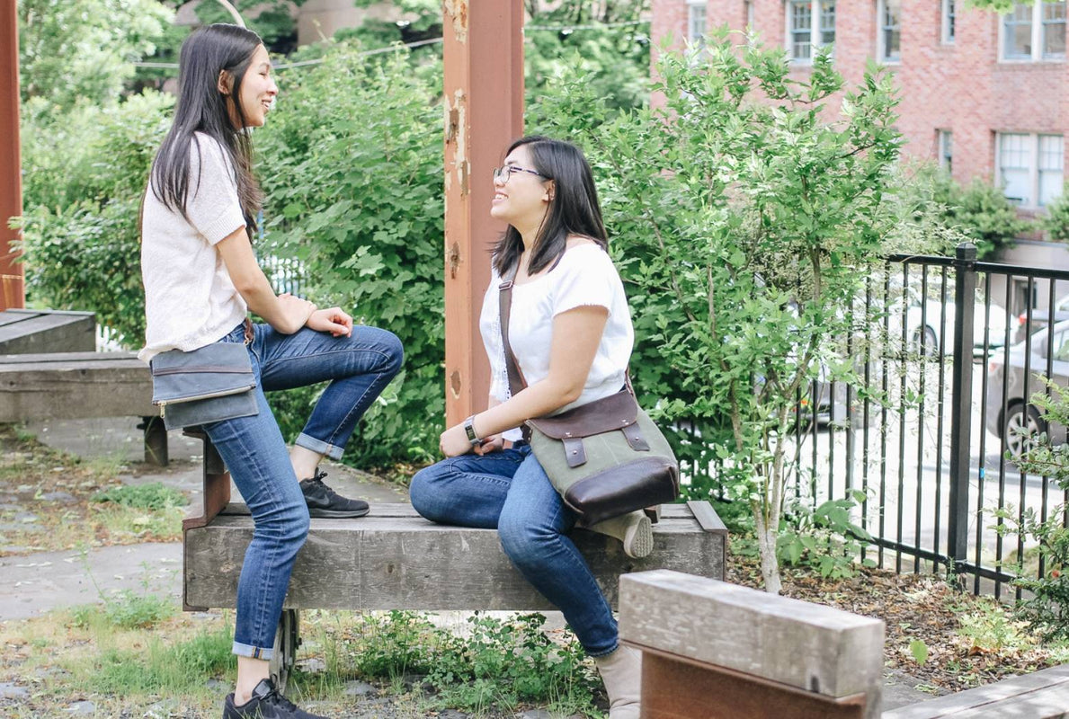 Two women talking in a park each wearing Jo Rose Design handcrafted waxed canvas and leather bag