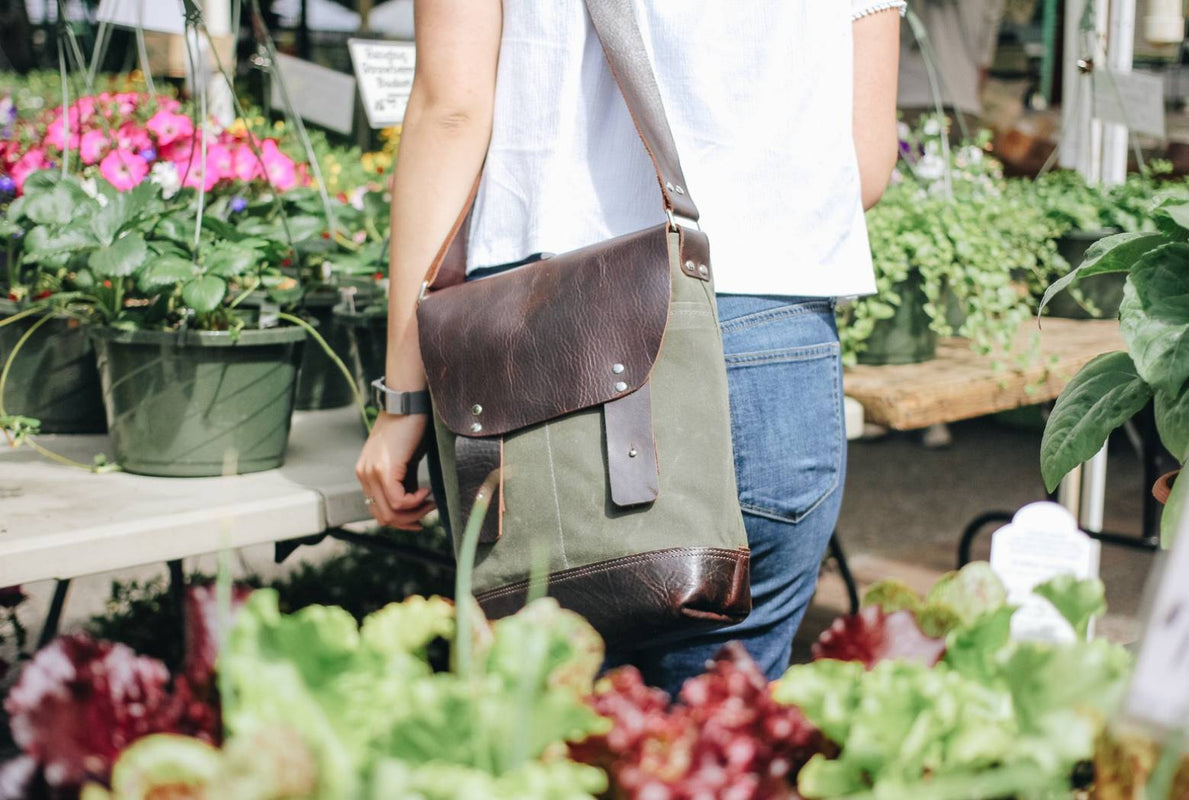 Woman carrying an olive green waxed canvas and brown leather messenger bag by Jo Rose Design while looking at flowers at a farmers market