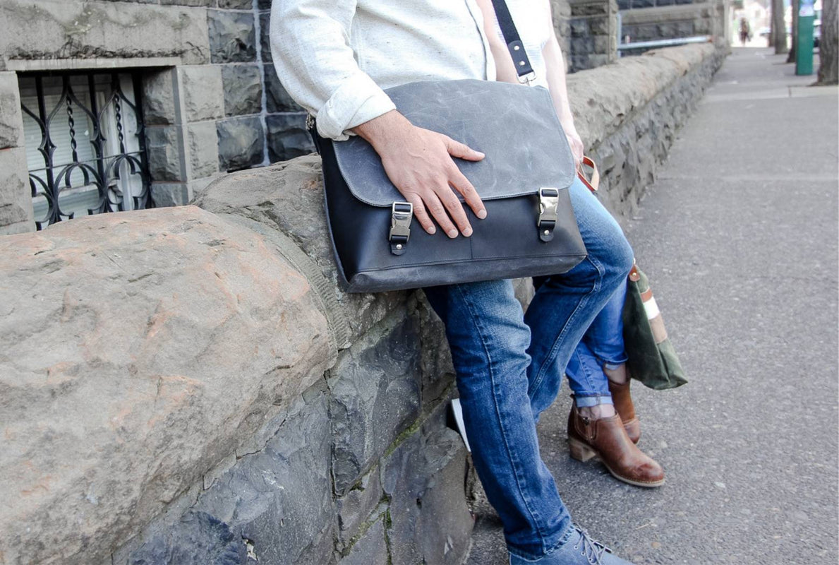 Man and woman resting against a rock wall while the man carries a charcoal waxed canvas and black leather laptop bag made by Jo Rose Design