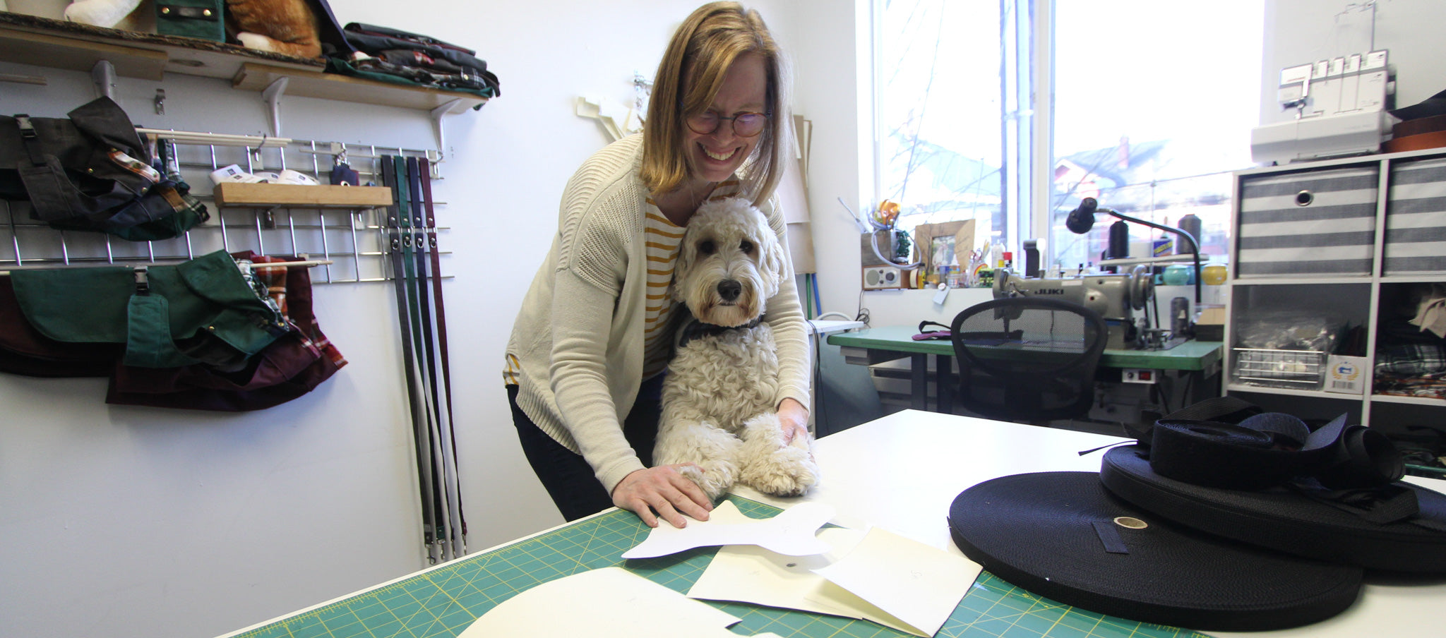 Woman standing with dog whose paws are on a sewing table