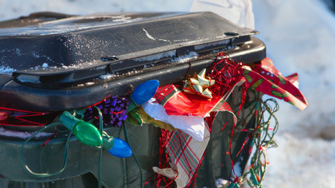 Garbage can overflowing with Christmas waste.