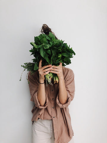 Woman holding lots of greens