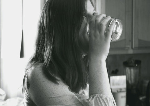 This is a black and white image of a woman standing in the kitchen drinking a glass of water. The woman has long hair.