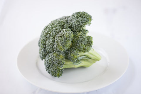 This is an image of a raw head of broccoli sitting on a white plate.