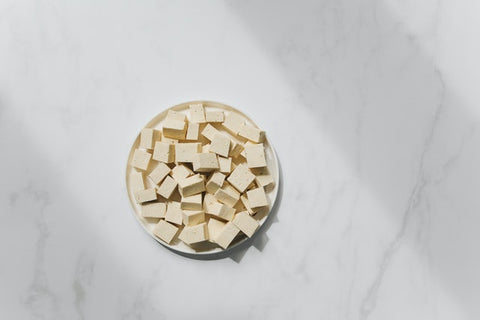 This is an image of tofu cut up in a bowl. The tofu is raw. The background is marble.