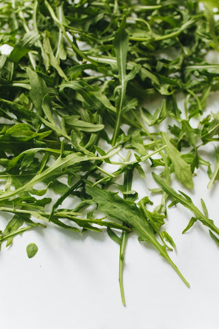 This is an image of a bunch of arugula sitting on a table.