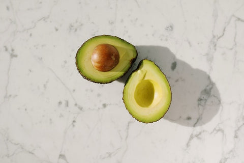 This is an image of a perfectly ripe avocado sliced open. It's on a marble background.