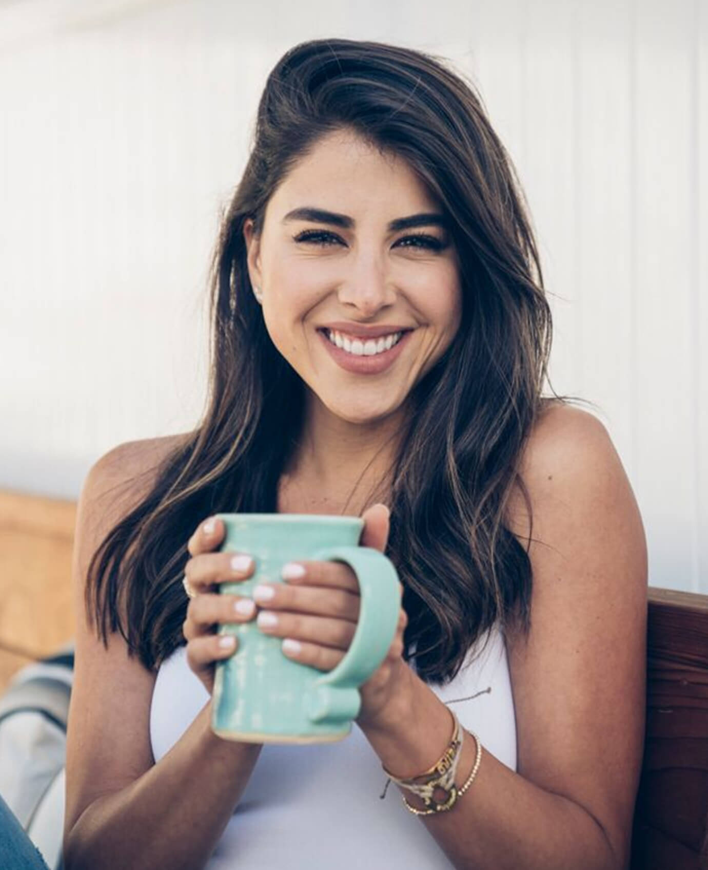 Daniella Monet holding a cup of coffee and smiling
