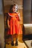 orange pinafore dress pom pom trim