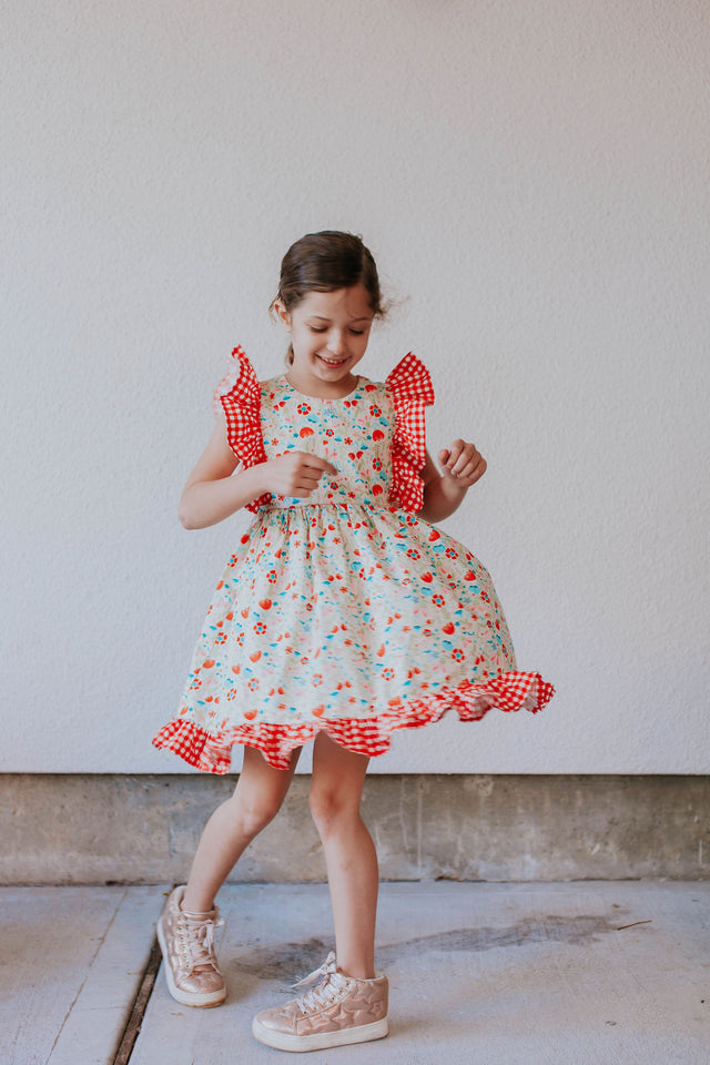little girl's red gingham and floral pinafore dress