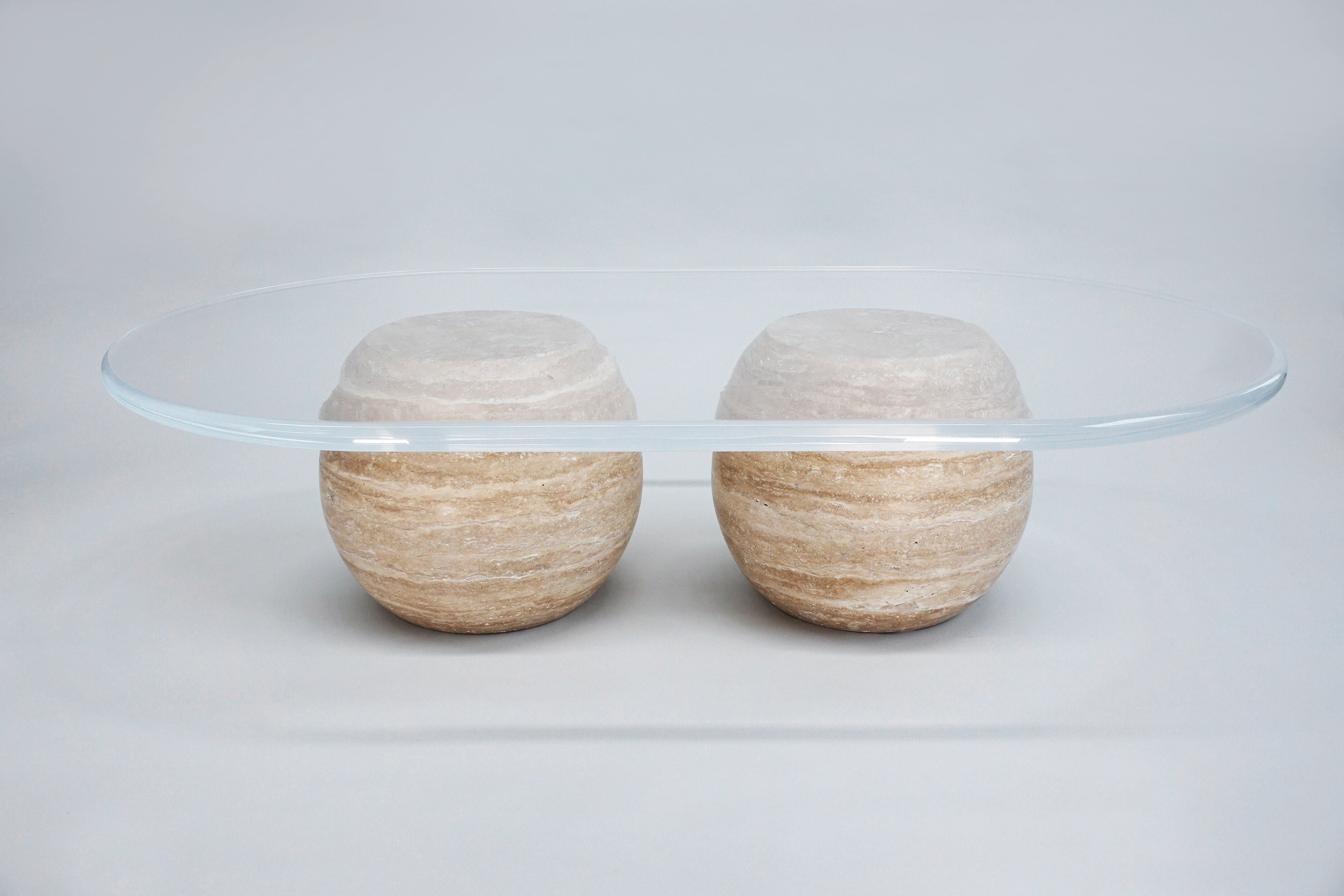 Le Ciel Coffee Table. A beautiful contrast of engineered and organic texture, the solid carved spherical travertine base showcases the incredible layered textures and tones of the organic stone.  The thick lucite tabletop offers a sense of weightlessness as the rounded edge creates an orbiting rim around the planetary nature of the design.