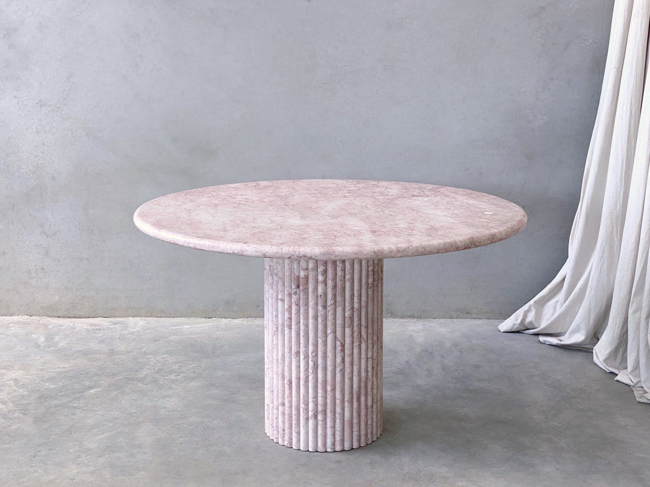 Rosetta Round Dining Table, Rosa Vene. The rounded edges and curved round shape married with the soft textures and pattern of veins throughout brings dimension and an elevated element of curated detail. Paired with fluted, scalloped cylindrical legs that are moveable so placement can be adjusted anyway desired.