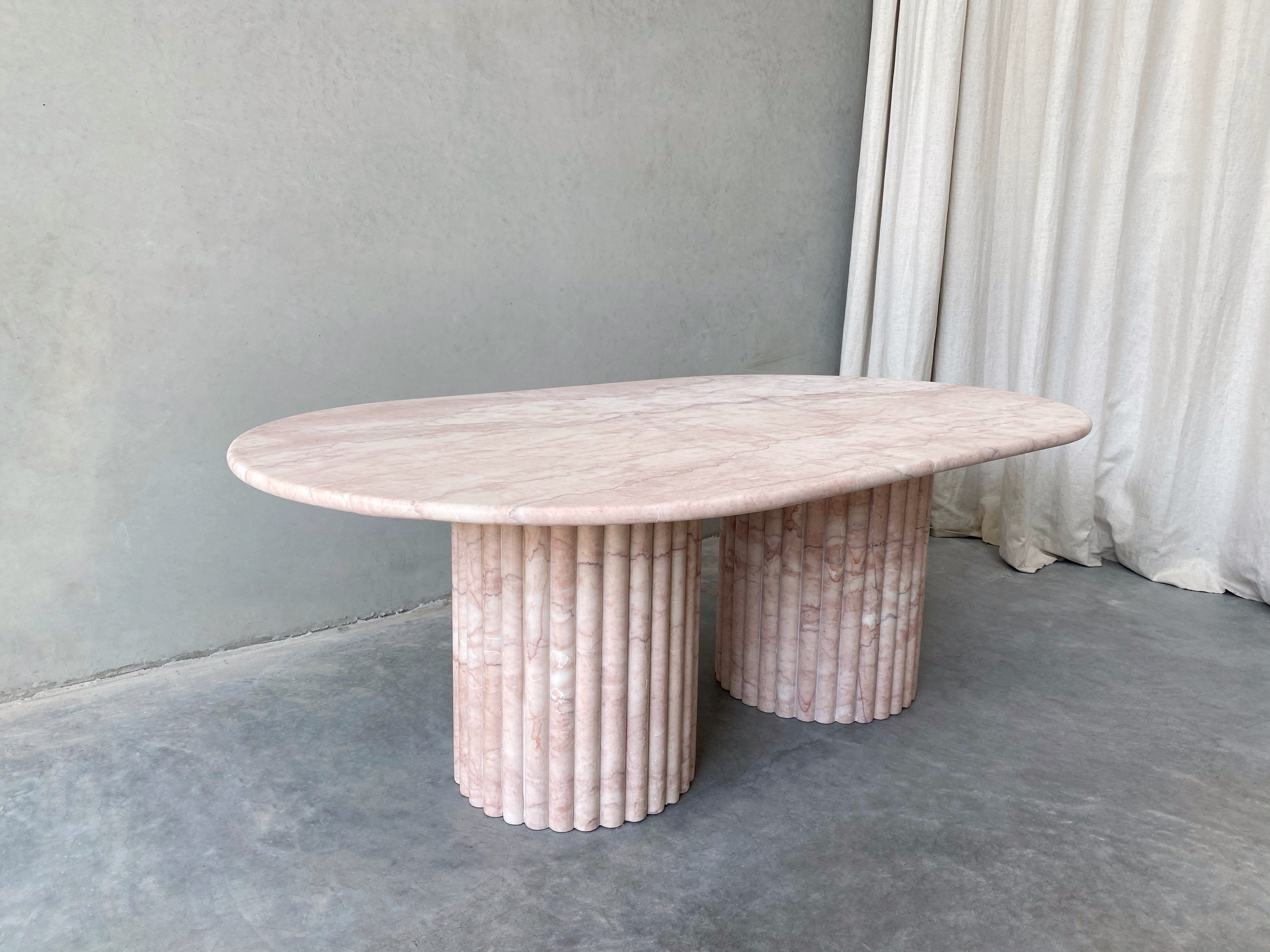 Rosetta Coffee Table, Rosa Vene. The rounded edges and curved oval shape married with the soft textures and pattern of veins throughout brings dimension and an elevated element of curated detail. Paired with fluted, scalloped cylindrical legs that are moveable so placement can be adjusted anyway desired.