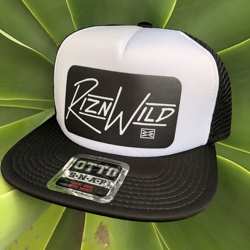 RIZNWILD | black and white trucker hat sitting on green agave fox tail plant
