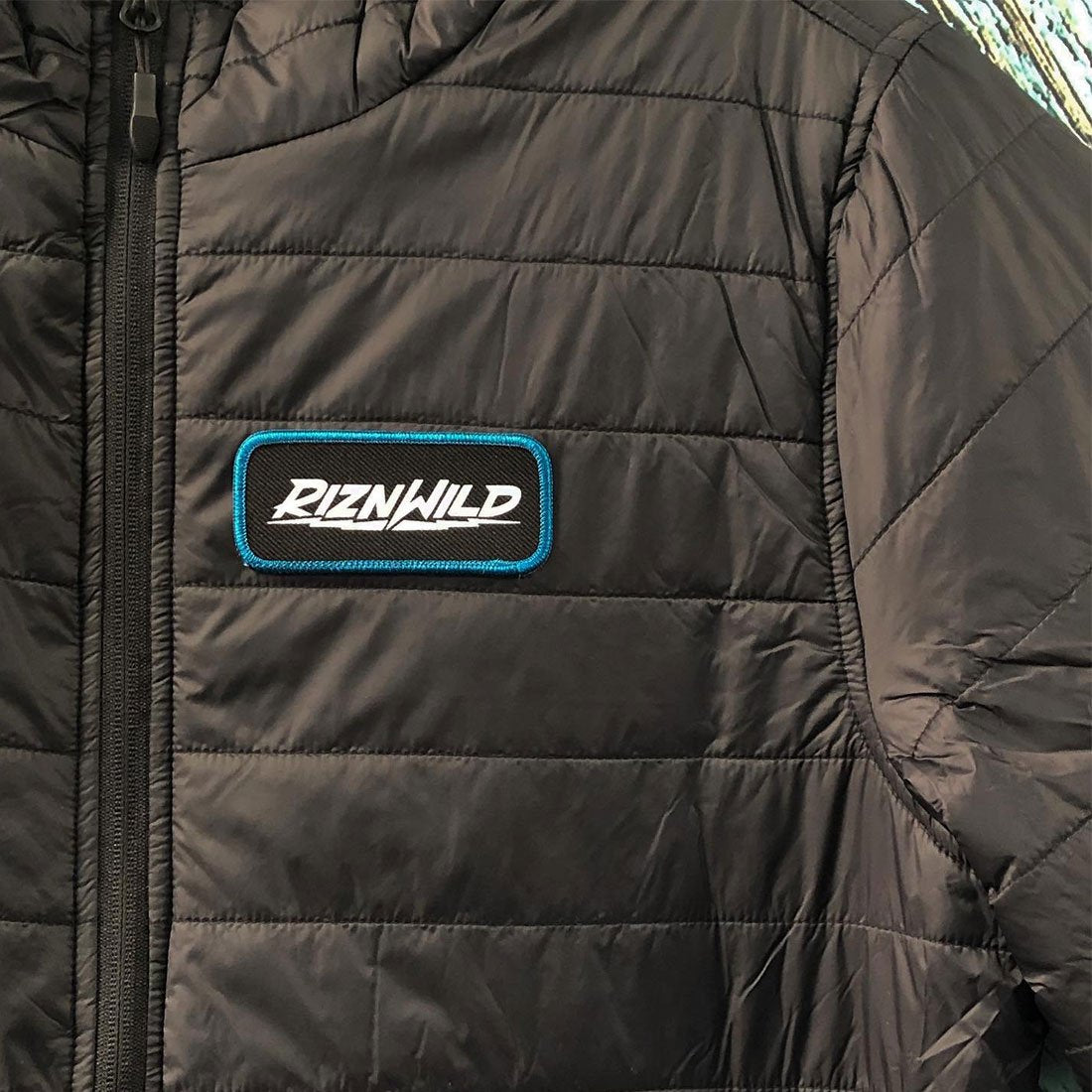 RIZNWILD | Close view of the puffer jacket patch sewn on