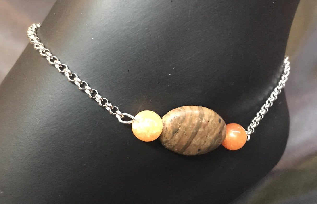 A single strand of agate beads in warm earth tones with an oval focal bead accents the stainless steel chain and stainless steel charms on this sturdy, rust-resistant anklet that goes with you on your adventures.
