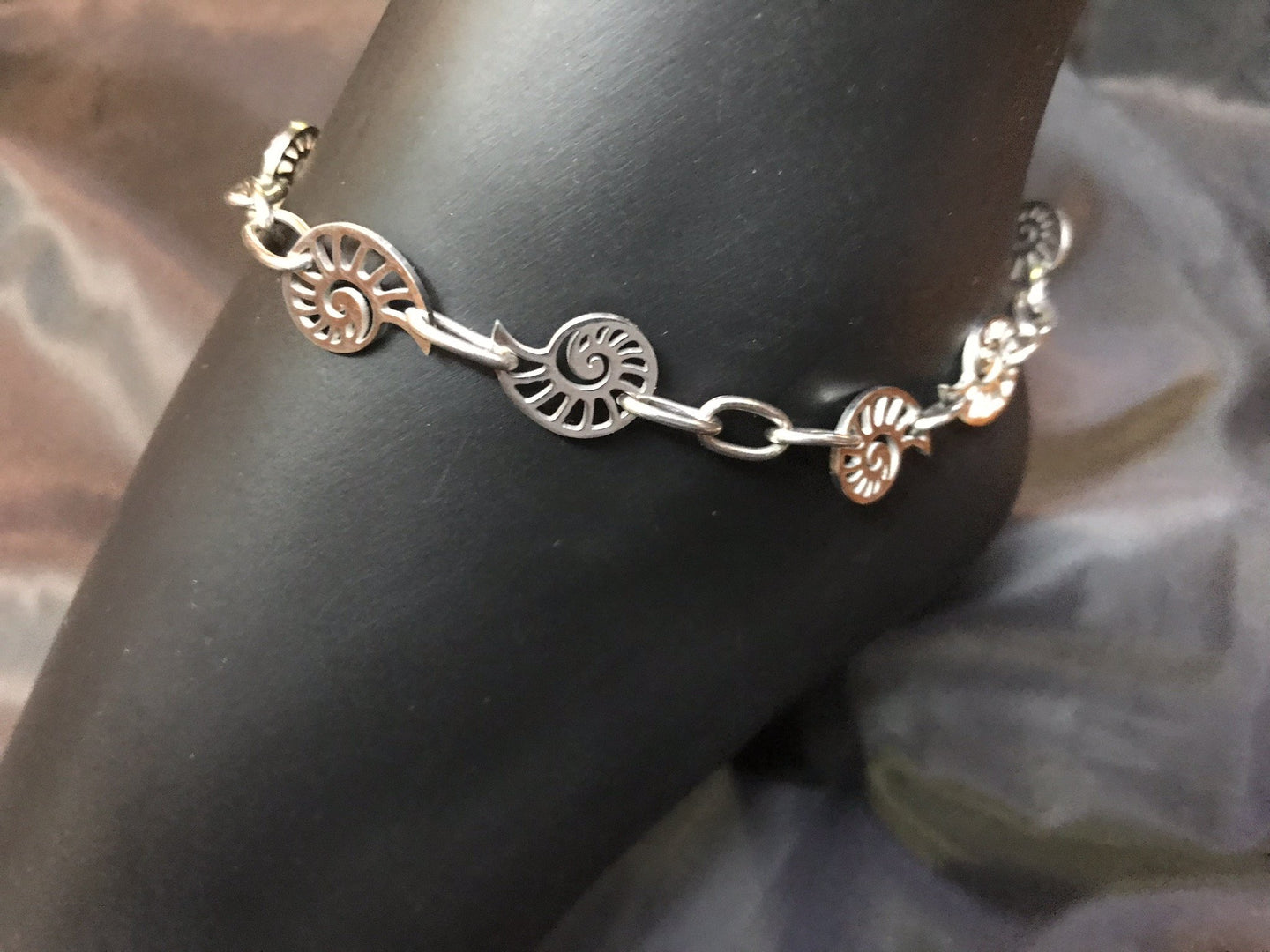 Delicate stainless steel nautilus charms form links in the chain in this rust-resistant anklet that can stay with you throughout all your adventures.