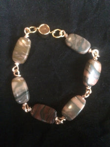"Six 20x11mm rectangular agate beads are connected with hand-wrapped plated copper wire to make this 7.5"" bracelet. The clasp is a no-slip magnetic mechanism that offers both security and ease of one-handed operation. It is designed to be a companion piece to matching earrings (Rectangular Swirl Wire Wrapped Agate Earrings - SKU 1EAR0013) and necklace (Rectangular Agate Wire Wrapped Necklace - SKU 1NCK0008) for a matching set."